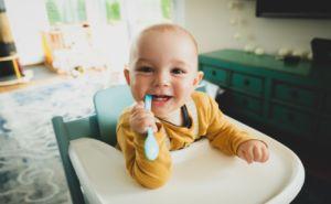 Baby mit Löffel beim Essen